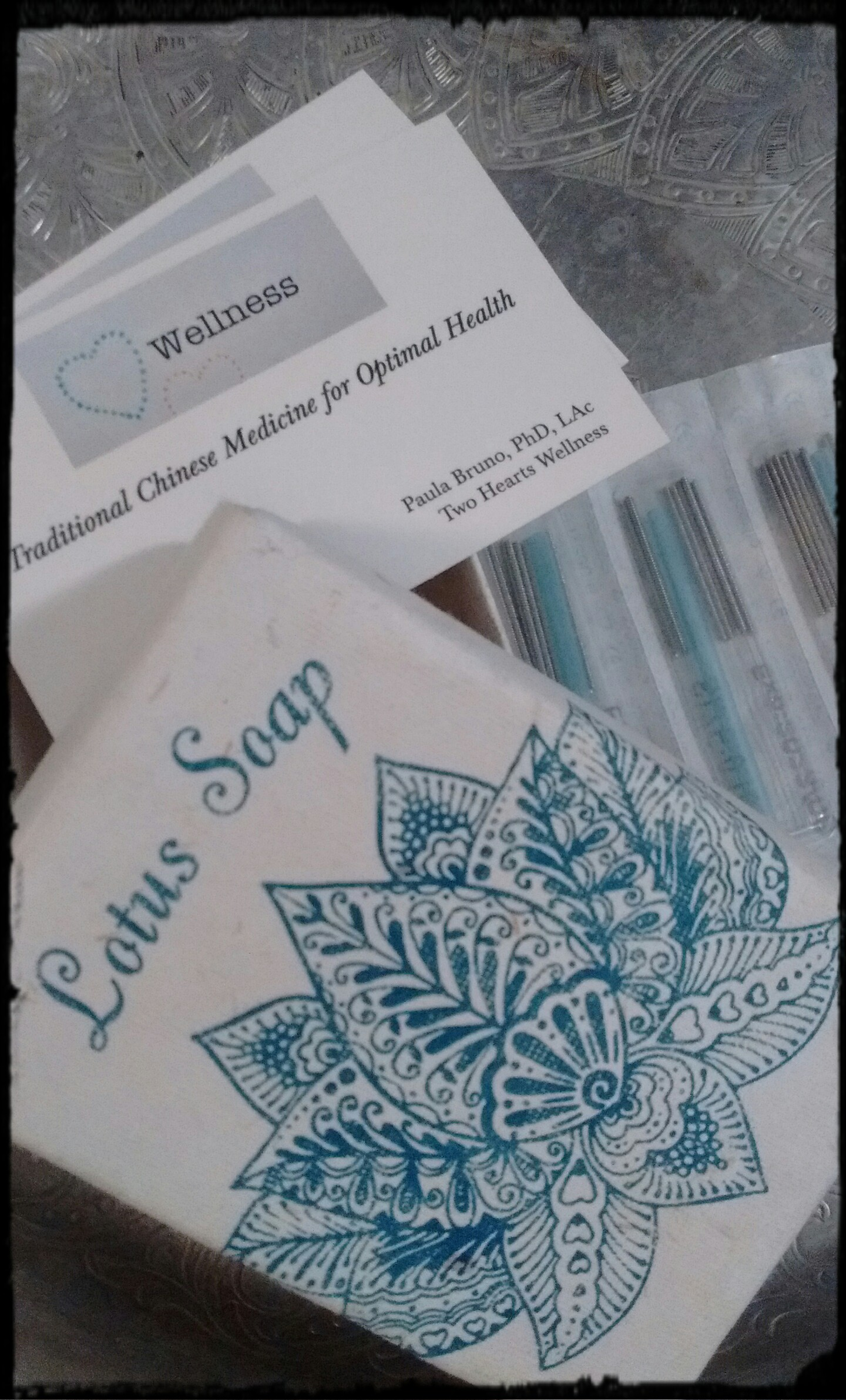 Two Hearts Wellness business card, acupuncture needles in 10-pack packets, & lotus soap package